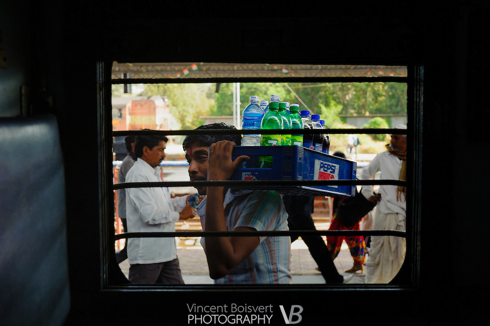 a soft drink vendor seen through a sleeper class train window