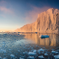 Greenland, Ilulissat, High resolution image of setting midnight sun lights massive iceberg from Ilulissat Kangerlua Glacier floating in Jakobshavn Icefjord on summer evening.