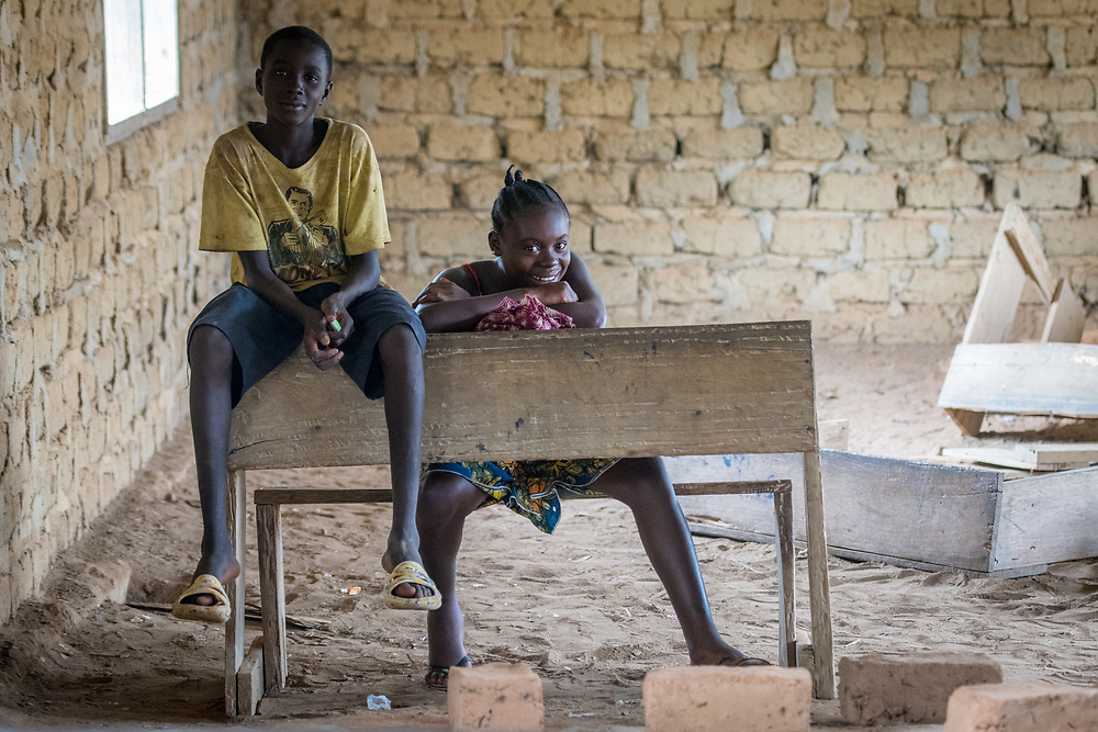A girl and boy smile while lounging at a desk in Ganta, Liberia