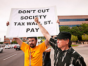 18 APRIL 2011 - PHOENIX, AZ: Men picket the offices of US Sen John McCain Monday. About 50 members of MoveOn.org gathered at the office of US Sen. John McCain (R-AZ) in Phoenix, AZ, Monday, Apr. 18, to draw attention to corporations that don't pay U.S. taxes. A representative of the group went into McCain's office present the Senator's staff with a tax bill for the 12 corporations they say paid no US income taxes.      Photo by Jack Kurtz