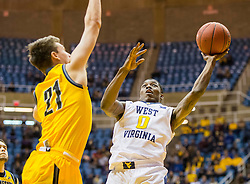Dec 5, 2015; Morgantown, WV, USA; West Virginia Mountaineers guard Teyvon Myers (0) shoots over Kennesaw State Owls guard Nick Masterson (21) during the second half at WVU Coliseum. Mandatory Credit: Ben Queen-USA TODAY Sports