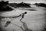 Dadaab refugeecamp - 90 kilometers from the somali border.<br /> the world biggest refugeecamp with apx. 300.000 people living there.<br /> <br /> a small girl collecting drinking water and brining it back to her family. Somalia.