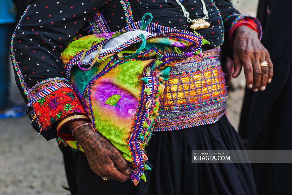 An old woman holds her colorful bag as she walks towards the wedding celebration in the village.