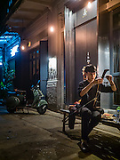 "27 JANUARY 2016 - BANGKOK, THAILAND: One of the house musicians tunes his ""Saw Duang,"" a two stringed Thai violin, in front of Tep Bar, a new bar and restaurant in the Chinatown neighborhood of Bangkok.       PHOTO BY JACK KURTZ"