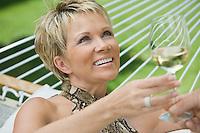 Woman holding wine in hammock