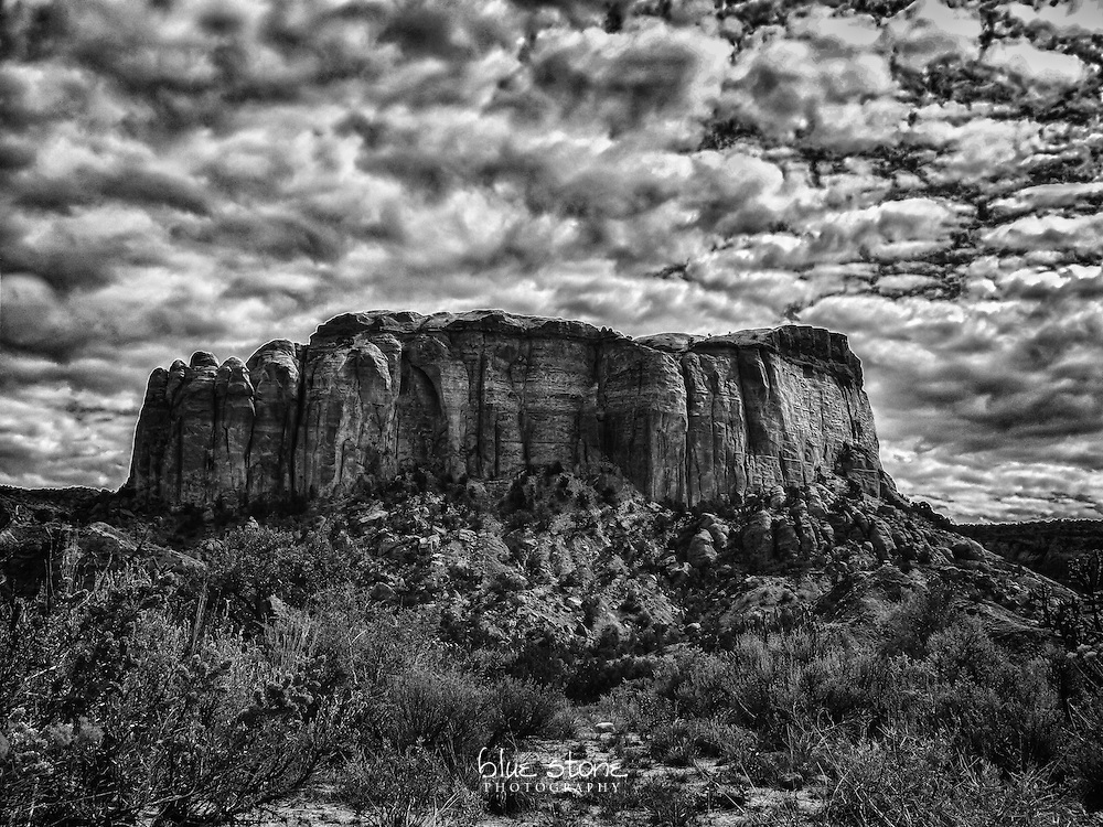 Black and white photograph of a granite outcrop near Ghost Ranch that is set against the clouds with desert grasses and cacti.<br />