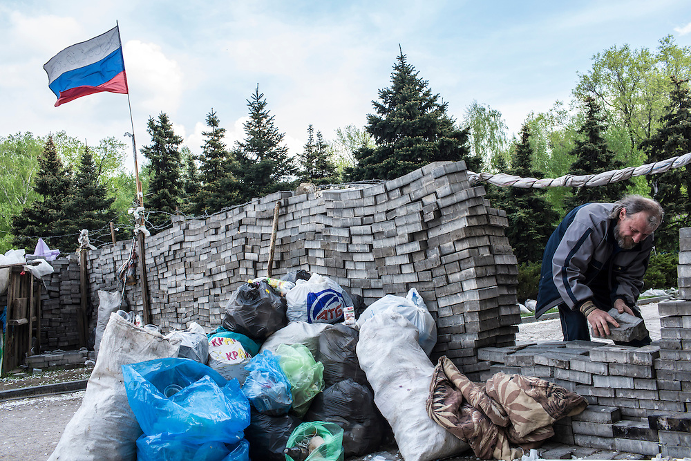 DONETSK, UKRAINE - MAY 4: A man uses bricks lifted from the sidewalk to build barricades outside the regional administration building, which is occupied by pro-Russian protesters, on May 4, 2014 in Donetsk, Ukraine. Cities across Eastern Ukraine have been overtaken by pro-Russian protesters in recent weeks, leading the Ukrainian military to respond with force in some areas. (Photo by Brendan Hoffman for The Washington Post)