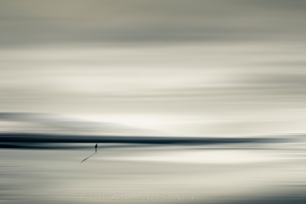 Abstraction of a man walking on an empty beach / plain<br />