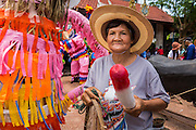 28 JUNE 2014 - DAN SAI, LOEI, THAILAND: Women with a wooden phallus in the Ghost Festival parade in Dan Sai. Phi Ta Khon (also spelled Pee Ta Khon) is the Ghost Festival. Over three days, the town's residents invite protection from Phra U-pakut, the spirit that lives in the Mun River, which runs through Dan Sai. People in the town and surrounding villages wear costumes made of patchwork and ornate masks and are thought be ghosts who were awoken from the dead when Vessantra Jataka (one of the Buddhas) came out of the forest.    PHOTO BY JACK KURTZ