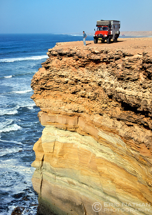 A man stands next to his Unimog overland truck on a cliff in southern Morocco.