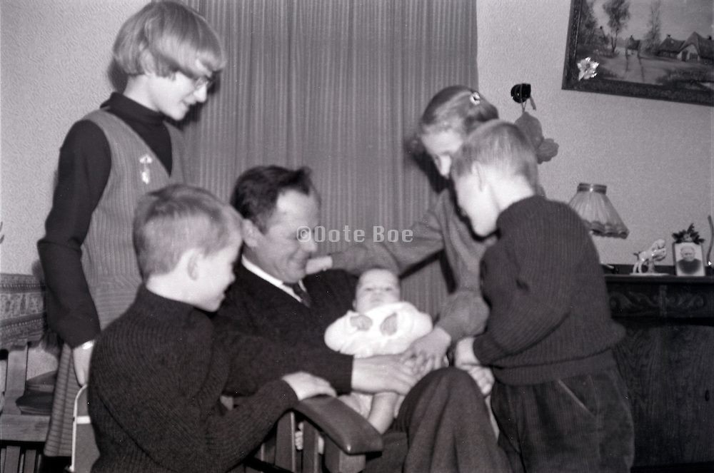 family moment father and children posing with newborn baby 1960s