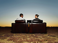 Two business people in armchairs in open plain at sunset
