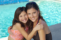 Girl embracing mother by swimming pool, portrait