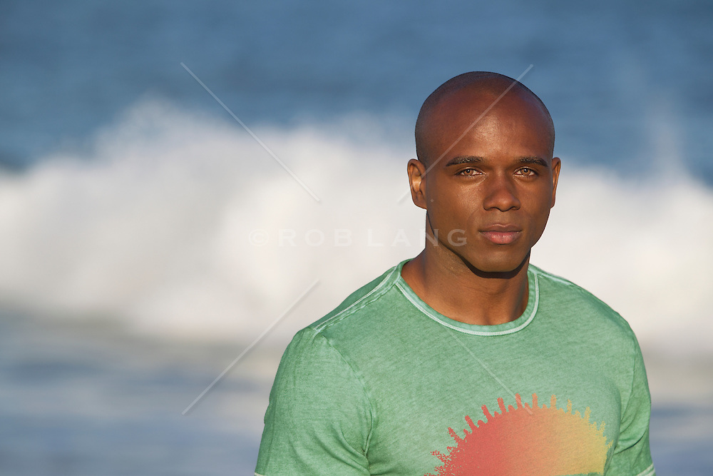 portrait of a handsome African American man with green eyes at the beach