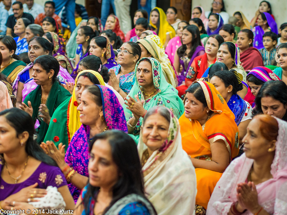 17 AUGUST 2014 - BANGKOK, THAILAND: Women pray during Krishna Janmashtami observances at the Vishnu temple in Bangkok. Krishna Janmashtami is the annual celebration of the birth of the Hindu deity Krishna, the eighth avatar of the Hindu god Vishnu. It is celebrated by Hindus in Thailand. There are about 53,000 Hindus in Thailand, most originally from India, but many Hindu deities are highly revered by Thai Buddhists and Hindu holy days are observed by many Thai Buddhists.     PHOTO BY JACK KURTZ