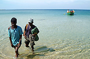 Africa. Mozambique. Niassa Province on the shores of Lake Malawi. Wading ashore from motor boat..CD0010