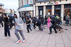 © Licensed to London News Pictures . FILE PICTURE DATED 07/08/2011. Enfield , UK . Riot police with dogs work to break up gangs of looters in Enfield Town Centre after hundreds gathered and broke in to shops following messages sent via Blackberry Messenger . Following a night of riots and looting in Tottenham , looting spreads to other parts of London . Photo credit : Joel Goodman/LNP