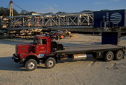 Large red flatbed transport truck parked at a work site
