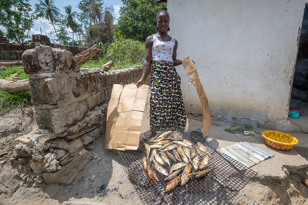 A woman smokes fish and poses for the camera in Ganta, Liberia