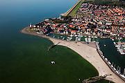 Nederland, Noordoostpolder, Urk, 08-09-2009. Voormalig eiland Urk, zicht op de jachthaven, vuurtoren en Kerkje aan Zee. Vissersplaats met grote vissersvloot, visafslag (veiling) en visverwerkende industrie. Streng gelovig dorp, veel verschillende  protestantse kerken en kerkgenootschappen. Het water ziet groen van de blauwalgen, de 'groene soep' of algenbloei is het resultaat van eutrofiëring (ten gevolge van de aanvoer van meststoffen uit de landbouw)..Former island Urk, fishing port and marina. Fishing village with fish auction and fish processing industry. Strict religious village, many Protestant churches and denominations. .(toeslag); aerial photo (additional fee required); .foto Siebe Swart / photo Siebe Swart