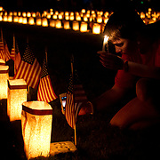 Kate Houghton, of Washington DC, takes a picture of one of the tombstones at the Soldiers National Cemetery, during the Sesquicentennial Anniversary of the Battle of Gettysburg, Pennsylvania on Sunday, June 30, 2013.  Thousands of flags were planted and candles lit as part of the Memorial Luminaria program at the cemetery.
