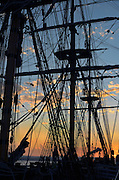 Sunset seen through the silhoette of the HMS Surprise, a replica of a British frigate purchased by the Maritime Museum after it was used in the film Master and Commander: The Far Side of the World, San Diego, California, USA