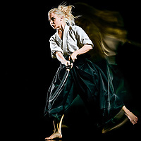 one budokas fighters woman practicing Iaido  Kenjutsu  studio shot isolated on black background