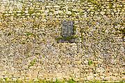 SANTILLANA DEL MAR, SPAIN - April 20 2018 - Stone wall texture with Christian crucifixtion cross symbol, Santillana del Mar, Cantabria, Spain.