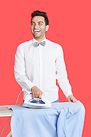 Cheerful man in formals ironing shirt over red background
