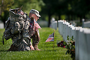"""Spc.Nicholas Tarento with the 3rd U.S. Infantry, pauses after placing a flag in front of the headstone of SSGT Chirstian Engeldrum in Arlington National Cemetery on Thursday. Members of the 3rd U.S. Infantry, known as The Old Guard, place American flags before gravestones and niches of service members buried at Arlington National Cemetery in advance of the Memorial Day weekend. The tradition, known as """"flags in,"""" is conducted annually since 1948. Tarento and Engeldrum were friends from the New York National Guard."""