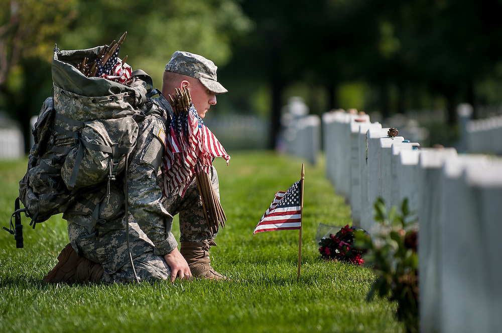 "Spc.Nicholas Tarento with the 3rd U.S. Infantry, pauses after placing a flag in front of the headstone of SSGT Chirstian Engeldrum in Arlington National Cemetery on Thursday. Members of the 3rd U.S. Infantry, known as The Old Guard, place American flags before gravestones and niches of service members buried at Arlington National Cemetery in advance of the Memorial Day weekend. The tradition, known as ""flags in,"" is conducted annually since 1948. Tarento and Engeldrum were friends from the New York National Guard."