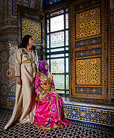 FEZ, MOROCCO - CIRCA MAY 2018:  Young Moroccan women in traditional dresses seating by a window in Fez
