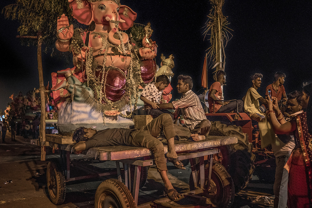 Exhausted man sleeps on a cart where a statue of Lord Ganesha has been loaded in line with dozens of others waiting to be lifted by a crane and immersed into the sea, symbolically returning them to nature as part of the Ganesh Chaturthi Festival.  Pondicherry, India.