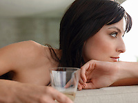Woman holding champagne glass indoors close-up