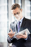 Businessman gesturing while using digital tablet in office