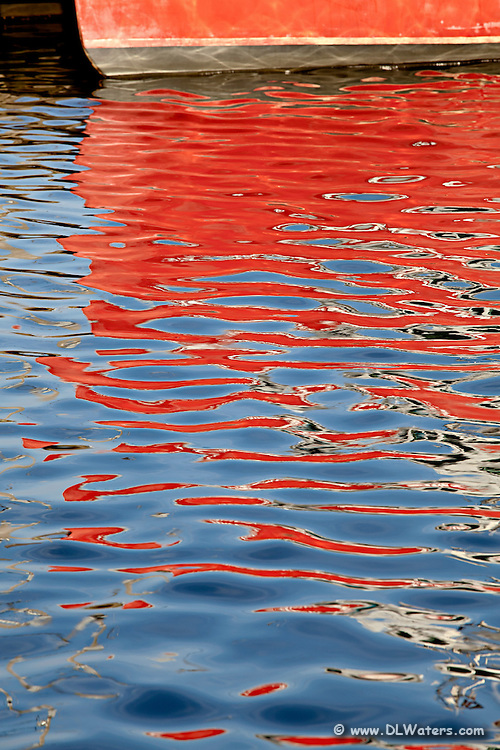 A red fishing trawler reflection in Wanchese Harbor.