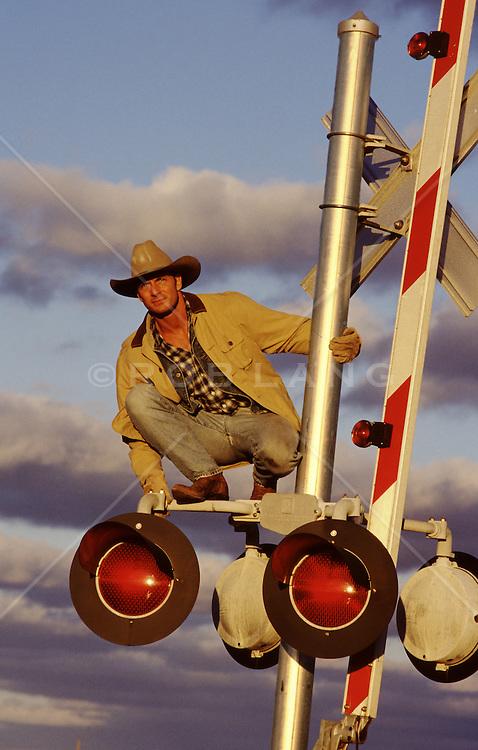 cowboy on top of a railroad crossing guard