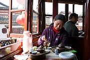 Woman drinking tea in the Huxinting Teahouse, Yu Garden Bazaar Market, Shanghai, China