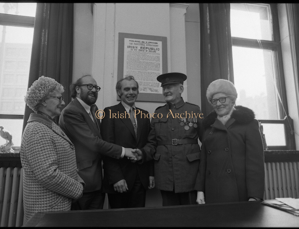 1916 Uniform Is Presented to The National Museum..(L8)..1977..23.04.1977..04.23.1977..23rd April 1977..Today Sean Duffy will parade his Irish Volunteer uniform for the last time as he wears it before he presents it to the National Museum, Kildare Street, Dublin. He wore the uniform on active service in the North Brunswick/North King Street theatre of operations in Easter Week 1916. He also managed to wear the uniform while held in detention in both England and Wales in the aftermath of the rising..Image shows Sean Duffy at the ceremony to present his uniform to the National Gallery. Included are from left, Ms Bridie Duffy (sister of Sean), Padraig O'Snodaigh, Assistant Keeper of the National Museum, Sean O'Teachrain, Keeper , Art and Industry Division, Sean Duffy and his sister Ms Annie Woods. On the wall behind them is a copy of the proclamation read out at the G.P.O.in 1916.
