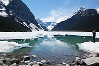 Tourist Photographing Partially Frozen Lake Louise During Spring Season, Banff National Park, Alberta, Canada