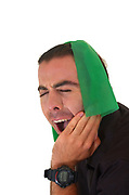Young male model with cloth wrapped around his head in pain due to a tooth ache on white background