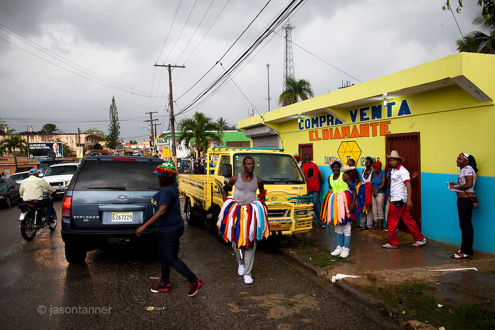 Dominican Republic: Residents of the former Batey, Haina look on as  Musicians, Dancers, Mayores and wait for rains to ease and perform as part of the GaGá  procession of El GaGá de San Luis....