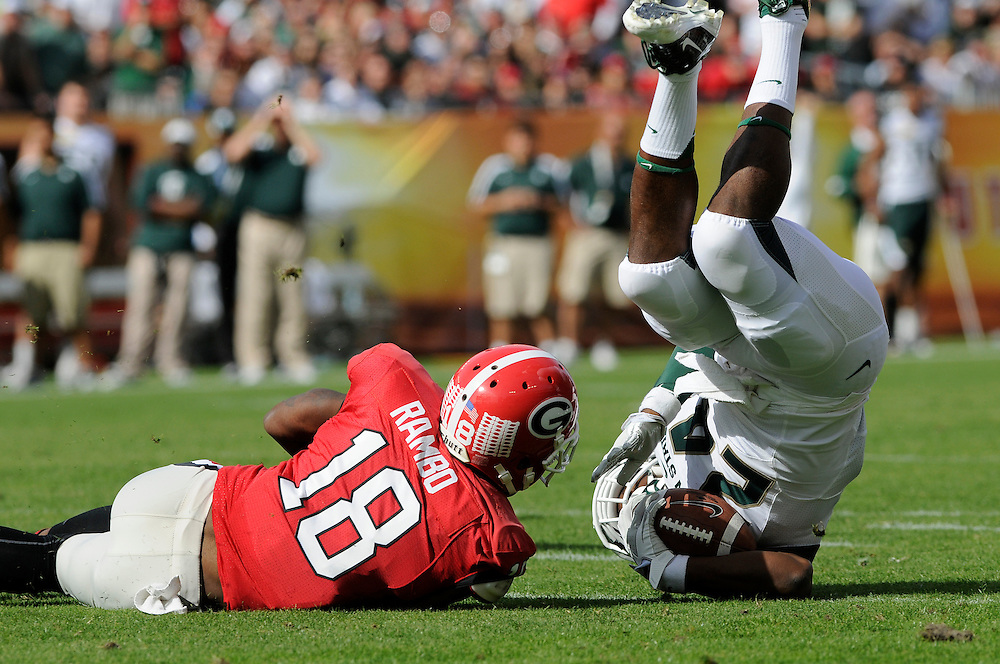 January 2, 2012: Bacarri Rambo of Georgia tackles Le'Veon Bell of Michigan State during the NCAA football game between the Michigan State Spartans and the Georgia Bulldogs at the 2012 Outback Bowl at Raymond James Stadium in Tampa, Florida.