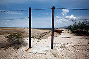 A hole, an open gate, in the barbed wire fence that separates Mexico from the US in El Paso, Texas.