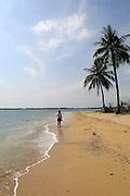 Woman walking by ocean and sandy tropical beach at Pasikudah Bay, Eastern Province, Sri Lanka, Asia