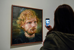 © Licensed to London News Pictures. 03/05/2017. London, UK.  A visitor to the National Portrait Gallery photographs a newly acquired portrait of the popular singer-songwriter Ed Sheeran, by artist Colin Davidson.  The 4ft x 4ft painting oil painting is the first portrait painted of the singer since the start of his professional career and has just been put on public display.   Photo credit : Stephen Chung/LNP
