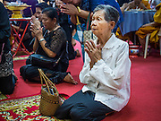 28 APRIL 2014 - BANGKOK, THAILAND: Women pray for Kamol Duangphasuk, 45, during the funeral for Kamol at Wat Samian Nari in Bangkok. Kamol was a popular poet who wrote under the pen name Mai Nueng Kor Kunthee. Kamol had been writing since the 1980s and was an outspoken critic of the 2006 coup that deposed Thaksin Shinawatra. After the 2010 military crackdown against the Red Shirts he went into temporary self imposed exile fearing for his safety. After he returned to Thailand he organized weekly protests against Thailand's Lese Majeste laws, which he said were being used to stifle dissent. Kamol was shot and murdered on April 23. The assailants are still at large but the murder is thought to be political.     PHOTO BY JACK KURTZ