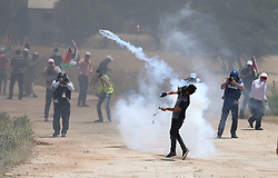 May 19, 2017 - Nablus, West Bank - A Palestinian protestor throws back a tear gas canister towards member of the Israeli soldiers during clashes at a protest in support of Palestinian prisoners on hunger strike in Israeli jails, in the West Bank village of Beit Dajan, near Nablus May 19, 2017. (Credit Image: © Ahmad Talat/NurPhoto via ZUMA Press)