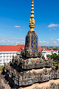 View of a spire adorning the Patuxay Monument, with the Office of the Prime Minister in the background, taken from the Patuxay Monument, Vientiane, Laos.