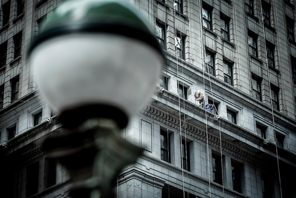 OFF THE WALL ST: Workers cleaning the facade of 100 Broadway next to NYSE - New York Stock Exchange.